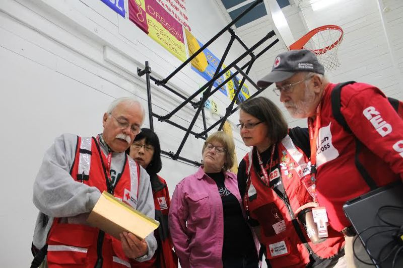 PMG FILE PHOTO: JOHN SCHRAG - Red Cross volunteers get their marching orders as they prepare to welcome displaced residents from the Scoggins Creek Fire near Gaston in 2014.
