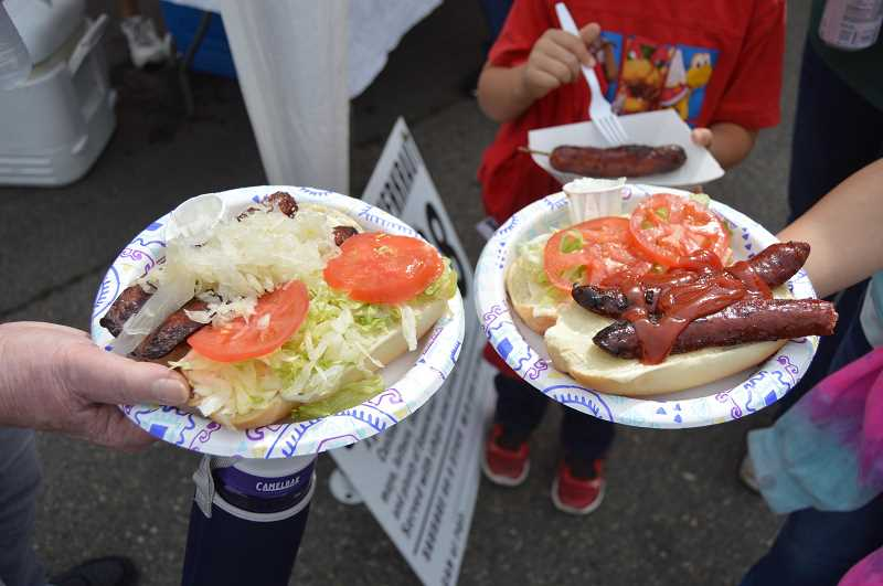 PMG FILE PHOTO - Hungry event attendees hold up their decked out Famous Scappoose Sandwiches featuring a grilled Octoberfest Sausage on a bun topped with sauerkraut, tomatoes and lettuce during the 30-year Scappoose Sauerkraut Festival held Sept. 14. The festival, dormant for five years following a 25-year run that started in 1999, will return in 2020.