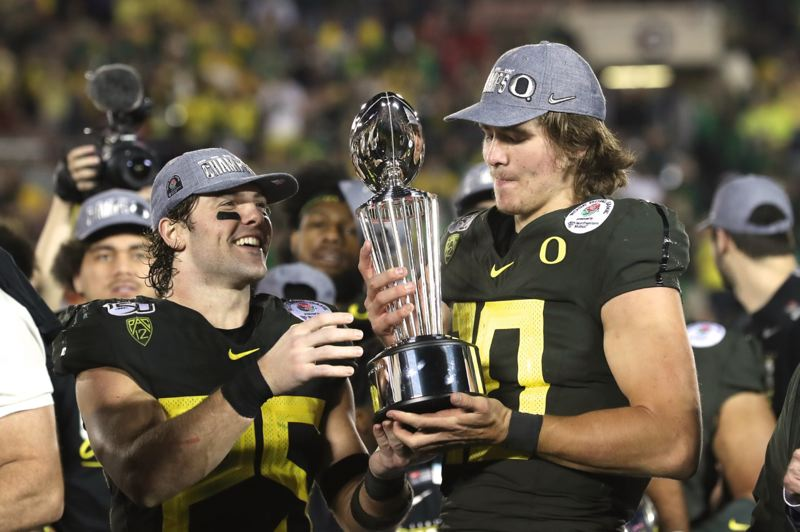 PMG PHOTO: JAIME VALDEZ - Oregon safety Brady Breeze (left) and quarterback Justin Herbert admire one of the spoils after the Ducks' Rose Bowl victory over Wisconsin.