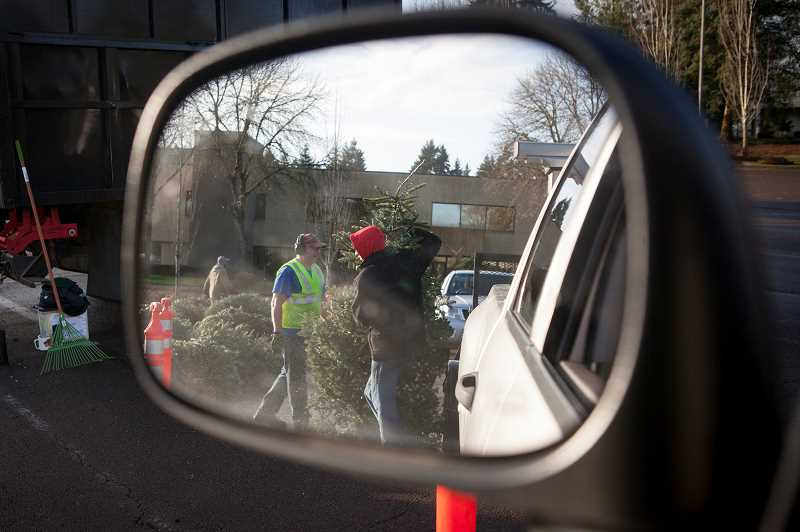 PMG PHOTO: JAIME VALDEZ - Scouts unload Christmas trees at the parking lot of the old Blockbuster building in Wilsonville.