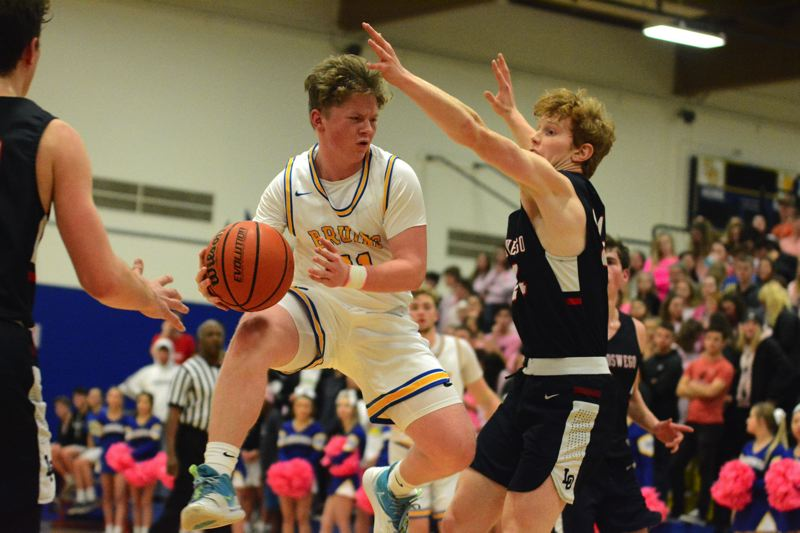 PMG PHOTO: DAVID BALL - Barlows Connor Hills goes airborne in the lane before sending a pass into the corner during the Bruins 60-54 overtime win over Lake Oswego on Tuesday.