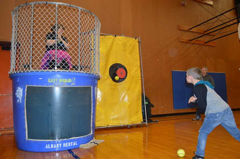 PMG PHOTO: CINDY FAMA - Ronald Hordichok attempts to dunk second grade teacher Karen Danielson-Groat.