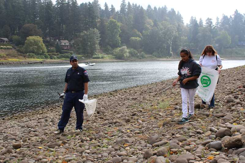 PMG FILE PHOTO - Volunteers clean up litter on Cedaroak Island. Volunteers play a big role in maintaining West Linn's parks.