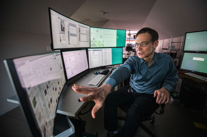PMG PHOTO: JONATHAN HOUSE - Graeme Newell, founder and CEO of 602 Communications, runs his home business with help from contractors spread around the world, whom he talks to using video conferencing. His desk where he writes and follows social media has 11 screens.