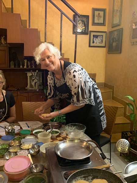 The women also took a cooking class to learn to make several Indian dishes. Joan Robbins adds the finishing touch to one of the dishes on the menu.