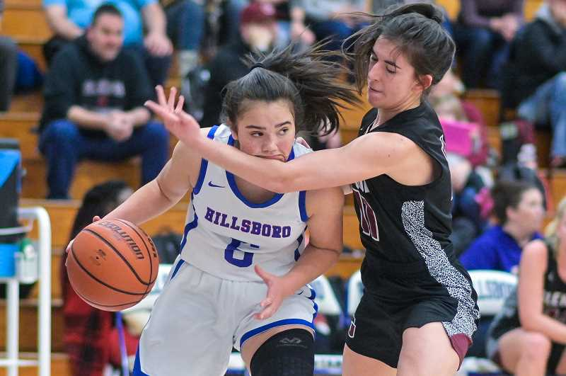 PMG PHOTO: CHRISTOPHER OERTELL - Hillsboro's Dylan Kem fights off Glencoe defender Maggie Gerber during the Spartans' game against Glencoe Wednesday night, Jan. 8, at Hillsboro High School.