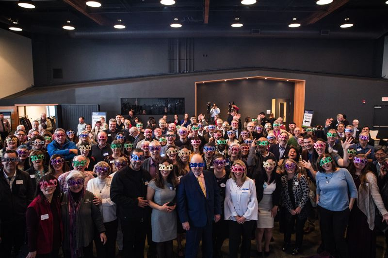 PHOTO BY BEN LAM - Beaverton Mayor Denny Doyle, center in dark jacket, and others sporting '2020' fake glasses, after Doyle concluded his state of the city talk Thursday, Jan. 9, at the Greatroom events space. The Beaverton Chamber of Commerce sponsored the event.