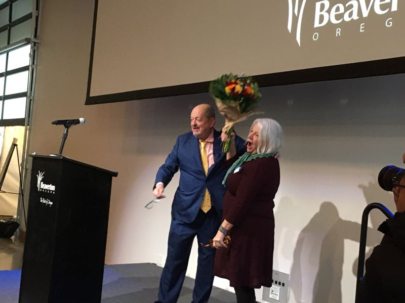 PMG PHOTO BY PETER WONG - Beaverton Mayor Denny Doyle gives a bouquet of flowers to his wife, Ann, to conclude his state of the city talk Thursday, Jan. 9, at Greatroom events space. The Beaverton Chamber of Commerce sponsored the event.