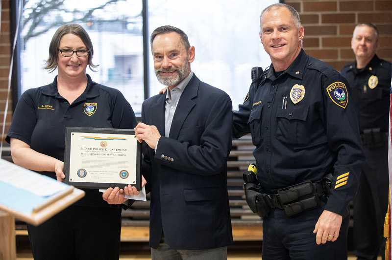 PMG PHOTO: JONATHAN HOUSE - Tigard Police Departments Jim Wolf is presented with the Distinguished Service Medal during his retirement party.