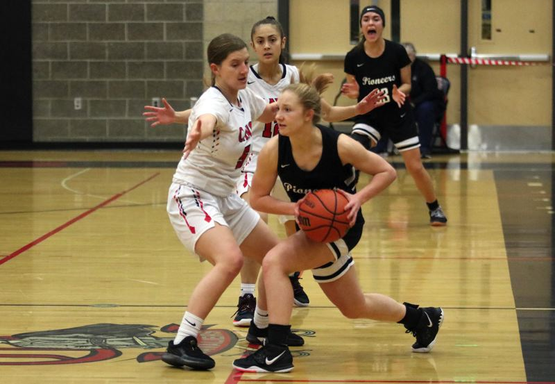 PMG PHOTO: JIM BESEDA - Sandy's Grace Lucky (with ball) looks to make a pass under pressure from Clackamas' Anna Henderson and Kalli So during the first half of Friday's Mt. Hood Conference girls basketball game.