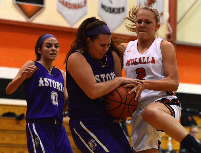 PMG PHOTO: DEREK WILEY - Molalla senior Maddy Lisac tries to rip the ball away from an Astoria player Friday night.