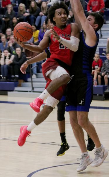 PMG PHOTO: JIM BESEDA - Clackamas CCs Robert Ford collides with Lanes Dylan Reichenberger as he drives to the basket during the first half of Saturdays NWAC mens basketball home game.