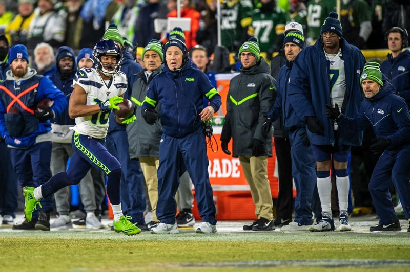 MICHAEL WORKMAN PHOTO - Seattle receiver Tyler Lockett picks up yards after a catch as Seahawks coach Pete Carroll and the bench watch during Sunday's NFL playoff game at Green Bay.