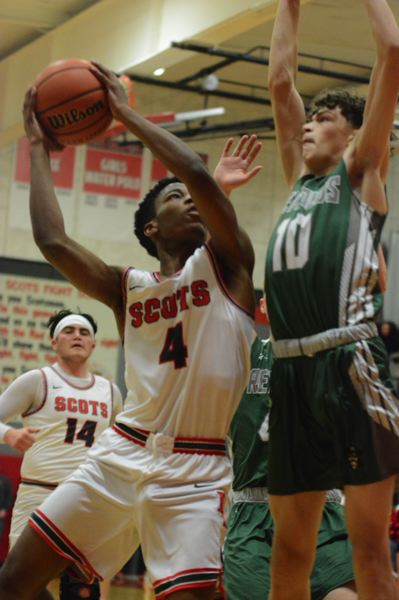 PMG PHOTO: DAVID BALL - David Douglas Emanuel Muange challenges Reynolds Keenan Coleman in a drive to the hoop in the first half of the Scots 79-66 win Friday night.