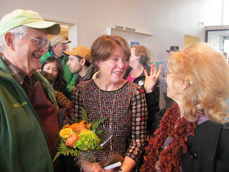 PHOTO BY DICK TRTEK - Tom Hogan, who heads up the Ledding Library's poetry program, and Jane Rickenbaugh, a longtime instructor at Clackamas Community College, congratulate Ledding Library Director Katie Newell at the reopening ceremony.