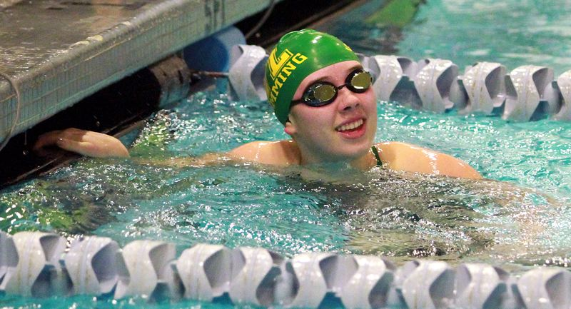 PMG PHOTO: MILES VANCE - West Linn freshman Anna Boyer smiles as she looks up at the scoreboard after winning the 50-yard freestyle race during her team's 106-63 victory over Lake Oswego at Lake Oswego School DIstrict Pool on Thursday, Jan. 16.