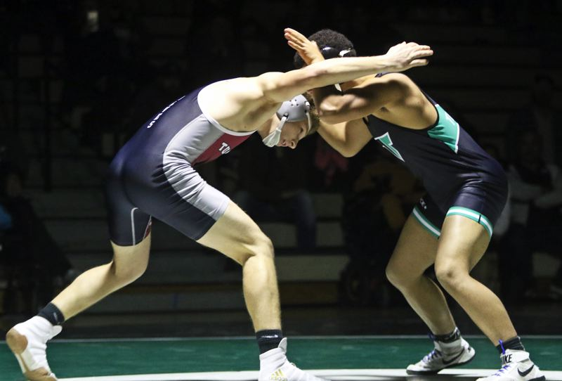 PMG PHOTO: DAN BROOD - Tualatin High School senior Jake Reser (left) locks up with Tigard's Kobe McClellen in the 170-pound bout at the teams' dual match. Reser won by fall to help the Wolves get a 40-32 team victory.