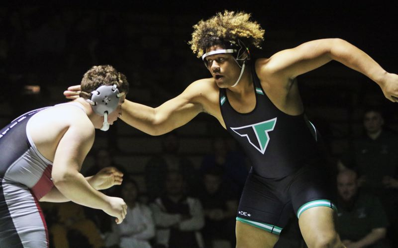 PMG PHOTO: DAN BROOD - Tigard High School senior Johnny Nomani (right) won by fall in the 285-pound match during the Tigers' Three Rivers League contest with rival Tualatin.
