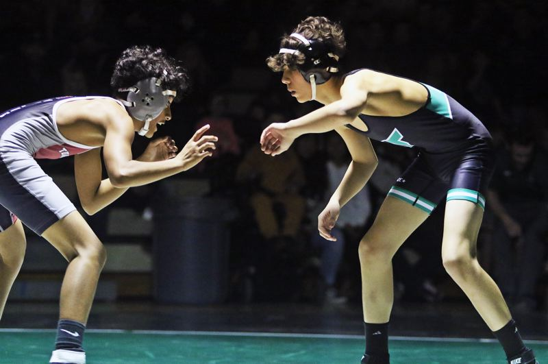 PMG PHOTO: DAN BROOD - Tigard High School freshman Adan Esquivel (right) gets ready to lock up with Tualatin's Darney Mottellang during their 106-pound match.