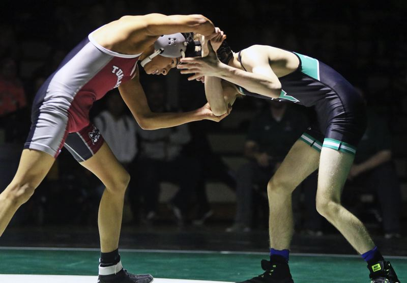 PMG PHOTO: DAN BROOD - Tualatin's Josue Guttierez (left) and Tigard's Atticus Waddell battle in the 113-pound match during the teams' Three Rivers League dual match.