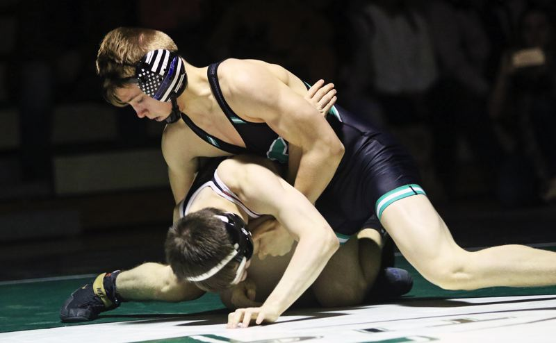 PMG PHOTO: DAN BROOD - Tigard High School freshman Chase Dennis (top) looks to go for a fall in the 132-pound match during the Tigers' league contest with Tualatin.