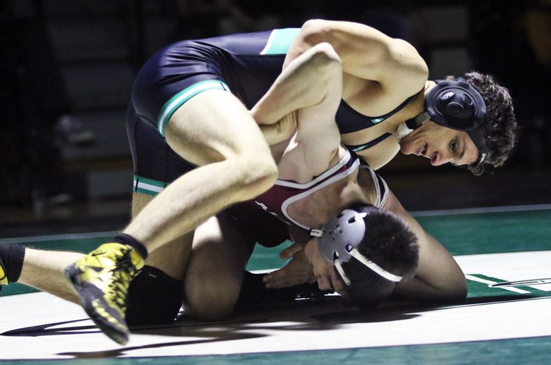 PMG PHOTO: DAN BROOD - Tigard High School freshman Timmy Cousineau (top) stays in control in the 138-pound match during the Tigers' Three Rivers League dual with Tualatin.