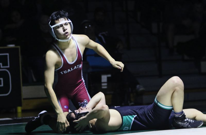 PMG PHOTO: DAN BROOD - Tualatin's Nathaniel Abarca-Lopez picked up a win by fall at 152 pounds during the Timberwolves' Three Rivers League dual match at Tigard.