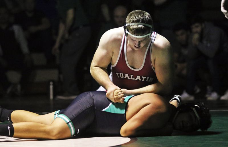 PMG PHOTO: DAN BROOD - Tualatin High School junior Curtis Strahm (top) won by fall at 220 pounds to clinch the dual match victory for the Wolves' in their bout with rival Tigard.