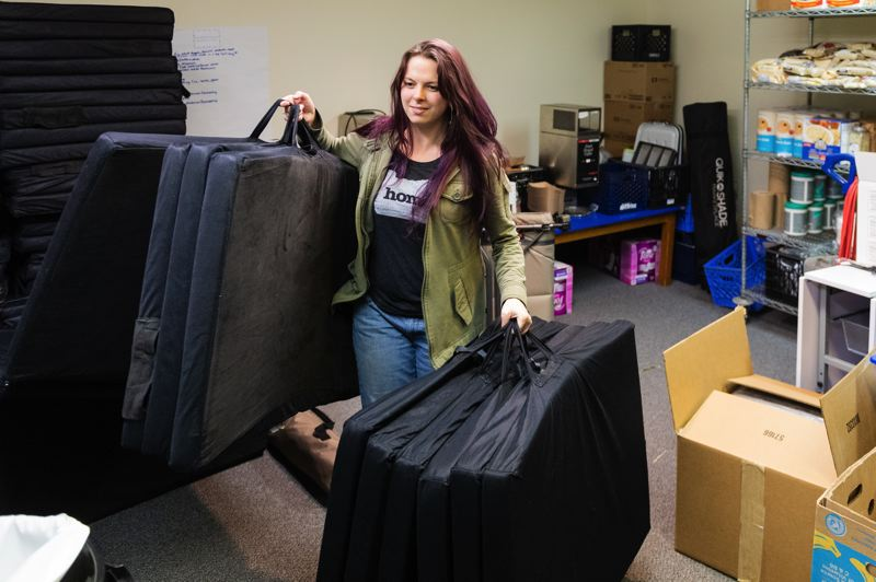 PMG PHOTO: CHRISTOPHER OERTELL - Celeste Goulding, director of the winter shelters in Forest Grove and Cornelius, brings out bed mats at for a night at the shelter in the Emanuel Lutheran Church.