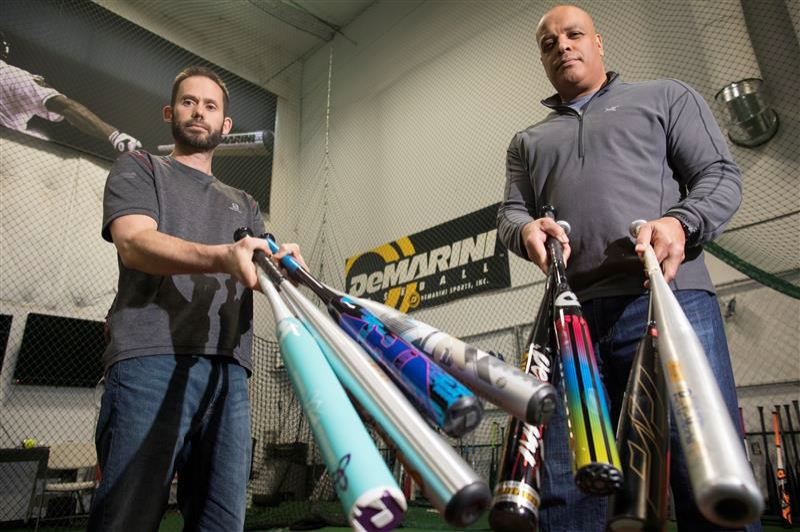 PMG PHOTO: JAIME VALDEZ - Nathan Baldwin, left, plant manager for DeMarini, and Jerry Garnett, manager of DeMarini's slow-pitch division, show off some of the bats the company has designed and manufactured over the past 30 years. ldwin, left, plant manager for DeMarini, and Jerry Garnett, manager of DeMarini's slow-pitch division, show off some of the bats the company has designed and manufactured over the past 30 years.