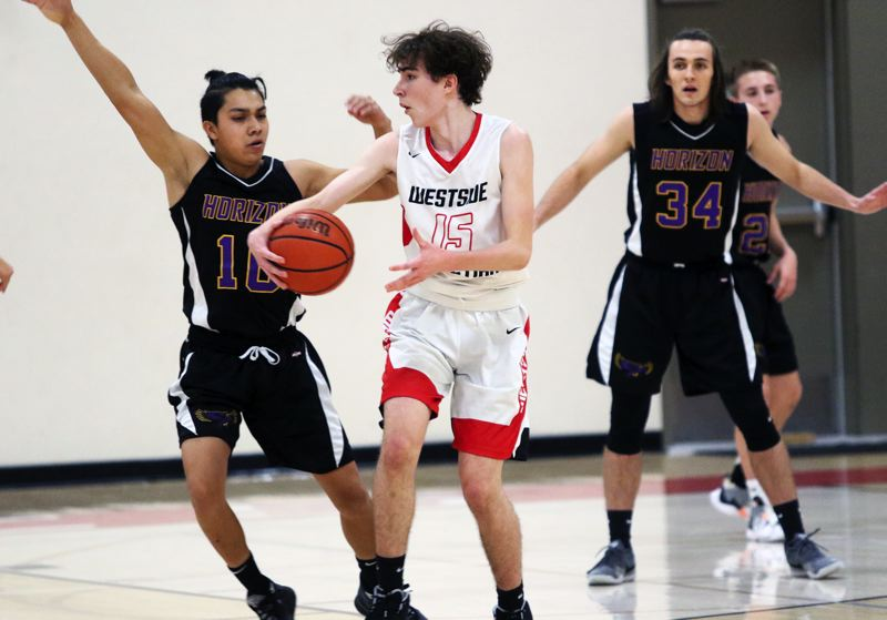 PMG PHOTO: DAN BROOD - Westside Christian High School junior Andrew Hollis (15) controls the ball at the high post for the Eagles during the 60-32 win over Horizon Christian in Saturday's Lewis & Clark League game.