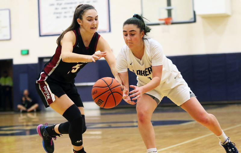 PMG PHOTO: DAN BROOD - Tualatin High School junior Aurora Davis (left) and Lake Oswego sophomore Kate Anders both go for thd ball during Tuesday's Three Rivers League opener. The Wolves got a 67-17 victory.