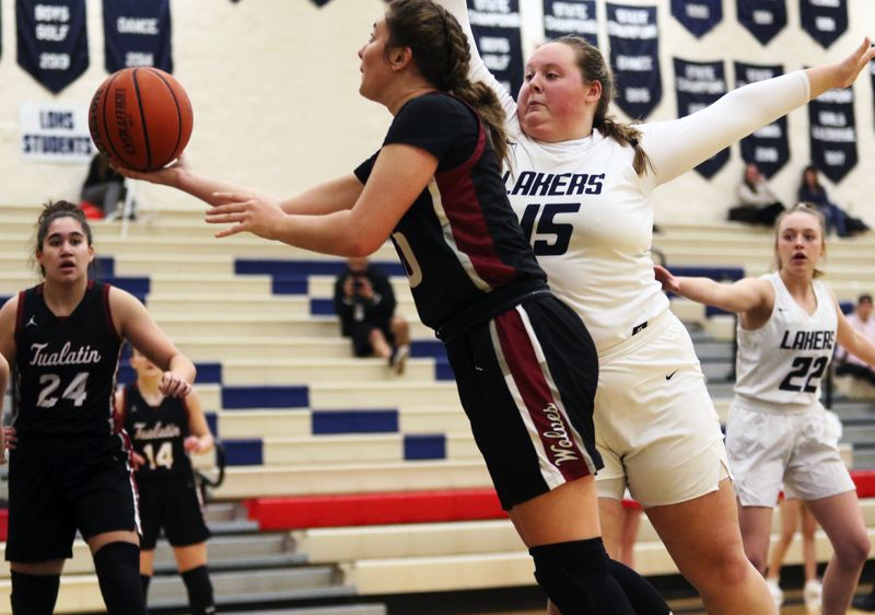 PMG PHOTO: DAN BROOD - Tualatin High School junior Kasidy Javernick (left) goes past Lake Oswego sophomore Lily Carlson and puts up a scoop shot during the Wolves' 67-17 win in Tuesday's Three Rivers League opener.