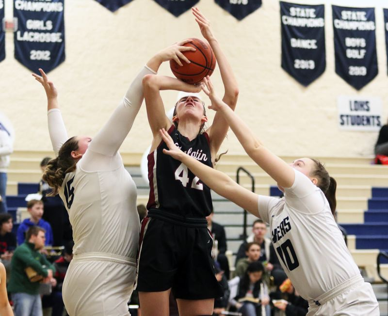 PMG PHOTO: DAN BROOD - Tualatin High School junior Natalie Lathrop (center) is fouled as she goes up for a shot during the Wolves' 67-17 win at Lake Oswego on Tuesday. Lathrop scored a game-high 18 points.