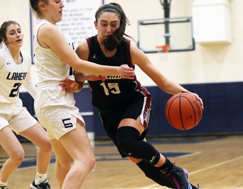 PMG PHOTO: DAN BROOD - Tualatin High School junior Aurora Davis (15) tries to drive to the basket during Tuesday's Three Rivers League opener at Lake Oswego. Davis scored 14 points in the Wolves' 67-17 victory.