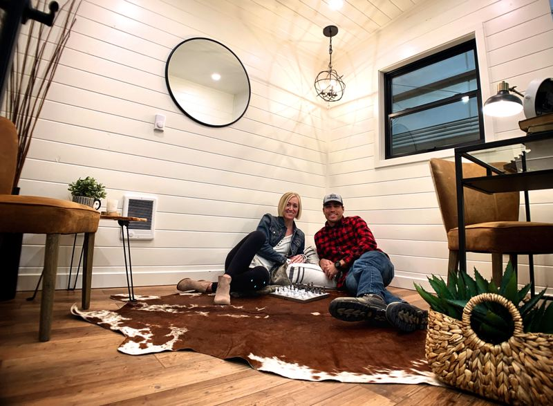 PMG PHOTO: JAIME VALDEZ - Anthony and Jamie Taylor-Weber stretch out in a model of the small outdoor structures they create that come complete with upscale decorating. The Tualatin couple run their business from an industrial park in Sherwood.