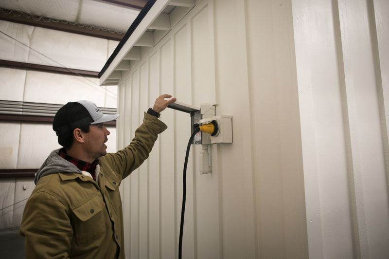PMG PHOTO: JAIME VALDEZ - Anthony Taylor-Weber shows how a RV-style plug is used to provide electricity to an Outdoor Office shed.