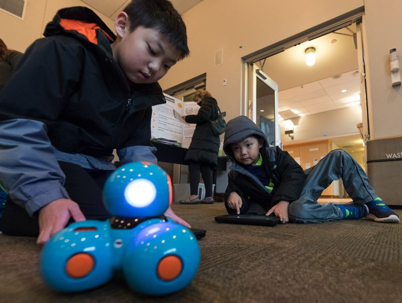 PMG PHOTO: JAIME VALDEZ - Micah Lim, 11, and his brother, Noah, 7, of Lake Oswego play with a Dash Robot during a Makerspace for Kids session at the Tualatin Public Library.