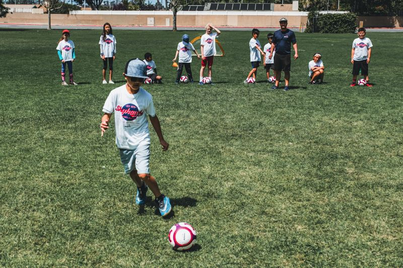 COURTESY PHOTO: SKYHAWK SPORTS - Kids practice dribbling exercises during a soccer camp put on by Skyhawks Sports Academy.