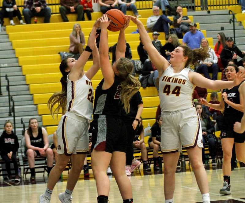 PMG PHOTO: WADE EVANSON - Forest Grove's Kayleen Dominguez (left) and Olivia Grosse (right) battle Glencoe's Megan Gaskin (middle) for a rebound during the Vikings game against the Crimson Tide Wednesday night, Jan. 15, at Forest Grove High School.