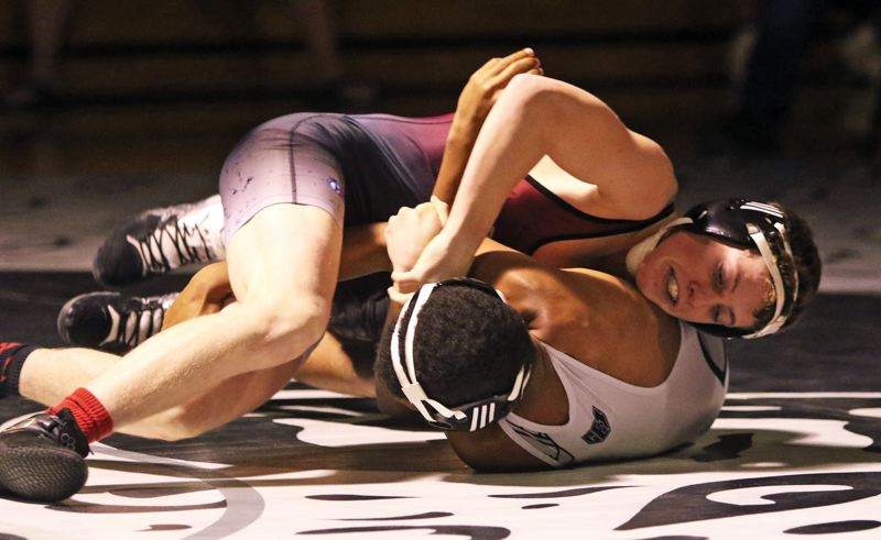 PMG PHOTO: DAN BROOD - Sherwood High School senior Nick Hekker (top) tries to turn Century's Nate Denman in their 120-pound match. Hekker got a first-round pin to help the Bowmen get a 37-33 victory.