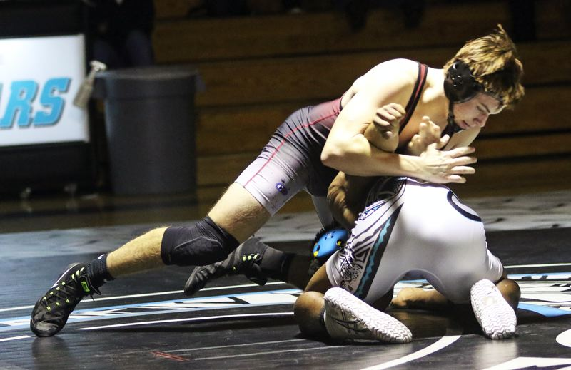 PMG PHOTO: DAN BROOD - Sherwood High School senior Brody Stevens (top) is in charge in his 160-pound match against Century's Jackson Wang. Stevens got a major decision victory to help the Bowmen win 37-33.