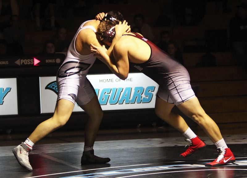 PMG PHOTO: DAN BROOD - Sherwood High School junior Bryan Cuthbertson (right) locks up with Century's Tau Tofeaono in their 220-pound match. Cuthbertson got an 11-5 decision victory.