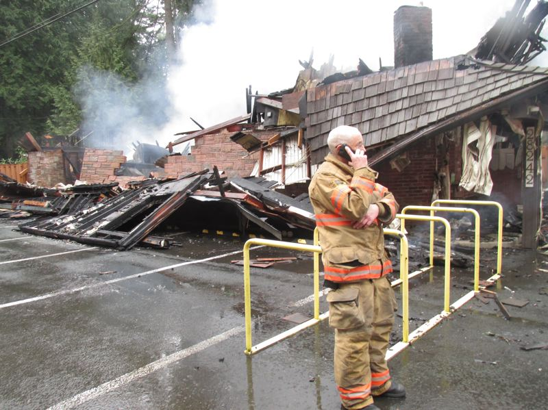 PMG PHOTO: SHANNON O. WELLS - A Corbett firefighter makes a call outside the devastation of Shirley's Tippy Canoe restaurant and lounge, which burned almost to the ground in a fire that started in the early morning hours of Friday, Jan. 17