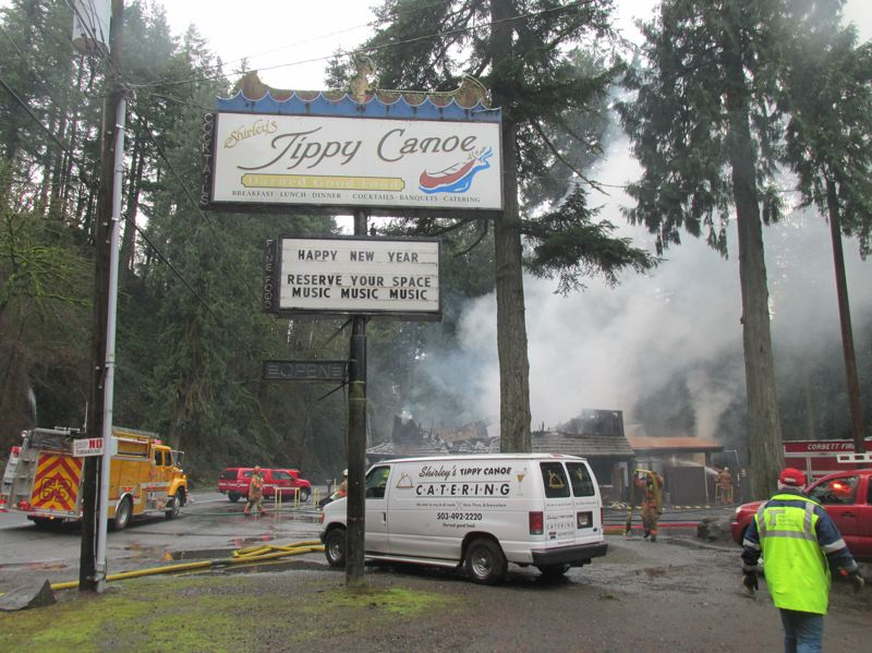 PMG PHOTO: SHANNON O. WELLS - The classic neon sign for Shirley's Tippy Canoe restaurant featuring a Native American rowing a canoe still stands tall on Historic Columbia River Highway after a fire devastated the two-story structure early Friday morning, Jan. 17.