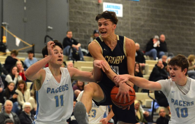 PMG PHOTO: DEREK WILEY - Canby junior Riley Knutson gets tied up with Lakeridge defenders Clark Sheehan, left, and Mason Nelson in the second half of Friday's game.