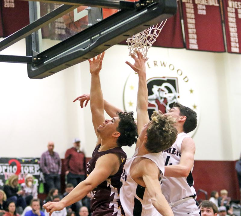PMG PHOTO: DAN BROOD - Forest Grove High School junior James Irvine (left) goes up to the basket during the Vikings' Pacific Conference game at Sherwood on Friday.