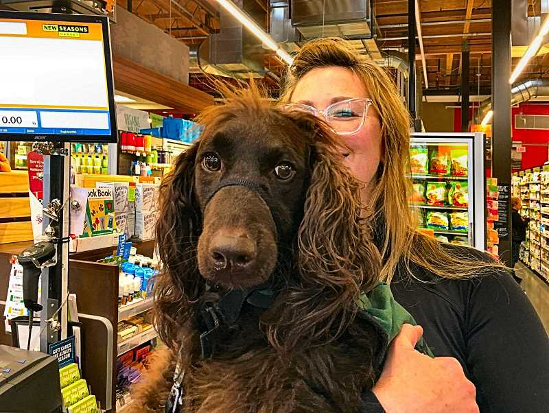 PAIGE WALLACE - Micaela Kennedy carries Vera, an autism service dog in training, through the checkout line at the Woodstock New Seasons store. Kennedy often teaches future service dogs to handle distracting situations by taking them to local businesses.