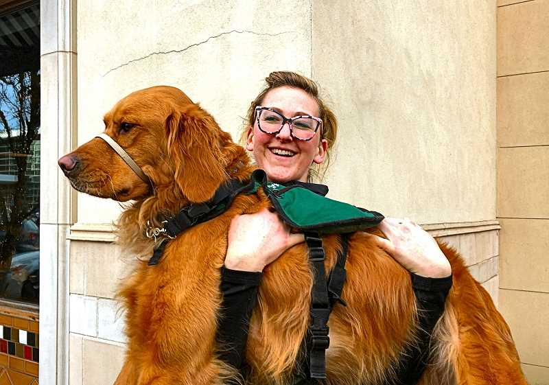 PAIGE WALLACE - Kennedy picks up Tucker after the golden retrievers graduation ceremony. Saying goodbye to a service dog shes trained is bittersweet, Kennedy said—a mixture of pride, sadness, and joy that the dog will help someone else live a better life.