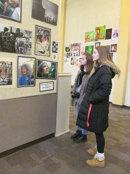 PHOTO BY ELLEN SPITALERI - Kristen Wesson and her friend Cassidy Galyon check out a display of photos in the arts building at Milwaukie High School.